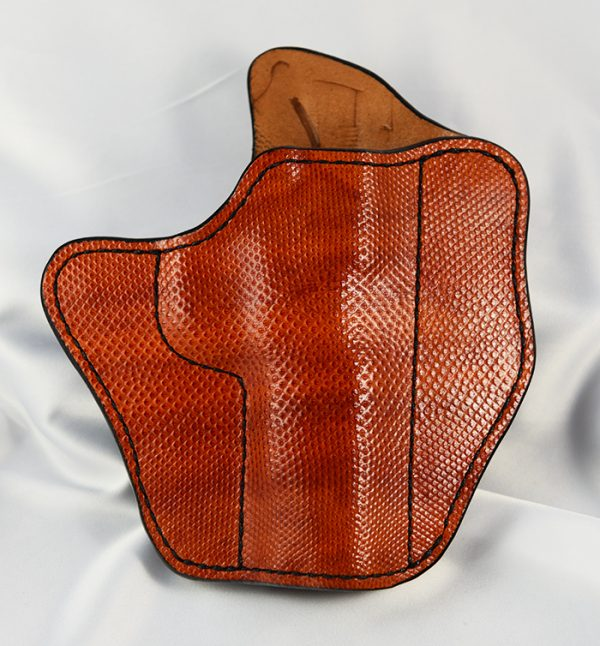 This Illusion holster is full coverage rust colored Sea Snake. It is for a commander length 1911 and is for a right handed shooter. This Illusion will fit an 1.5 inch belt and features FBI cant. The additional photo shows the slight high grain pattern that came out during finishing on the reverse side of the holster.